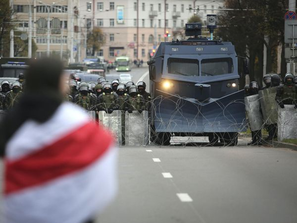 A protester draped in an old Belarusian national flag stands in front of a police line