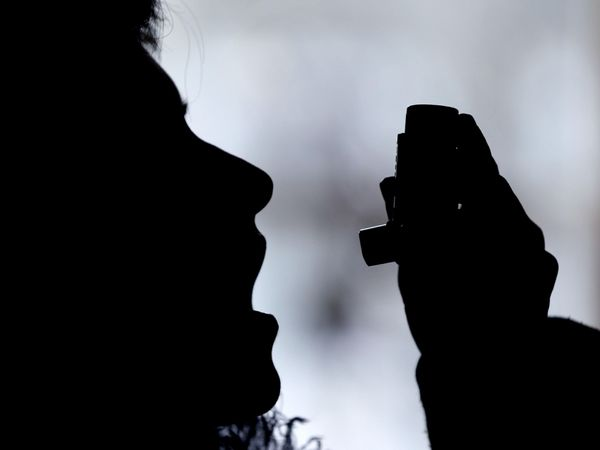 A person using an asthma inhaler