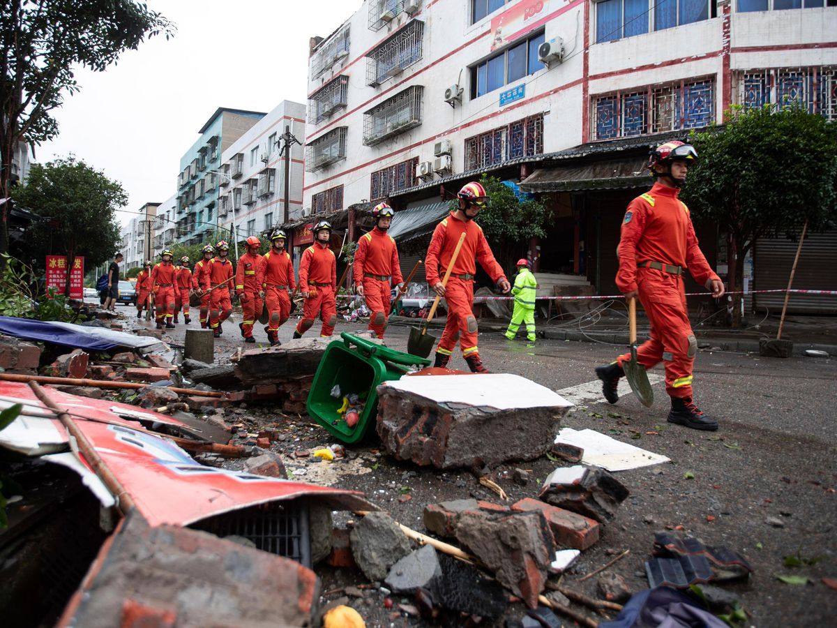 Rescue workers walk near debris in the aftermath of the earthquake