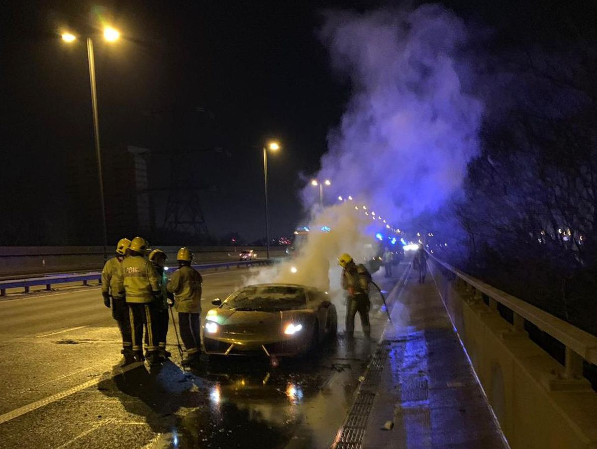 Firefighters attending to the smouldering supercar