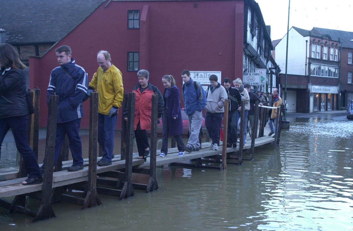 People make their way across the duck boards in Frankwell, Shrewsbury in December 2000