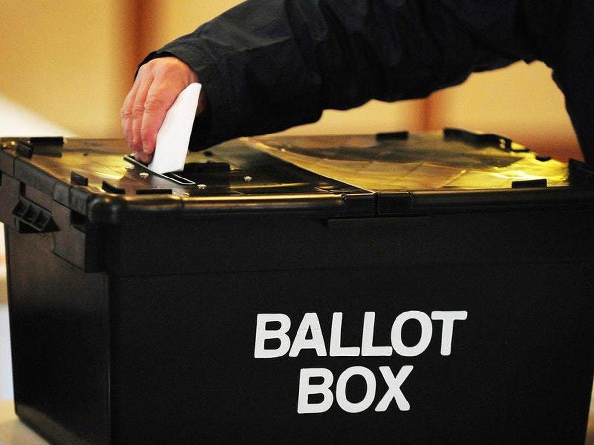 Man puts paper in ballot box