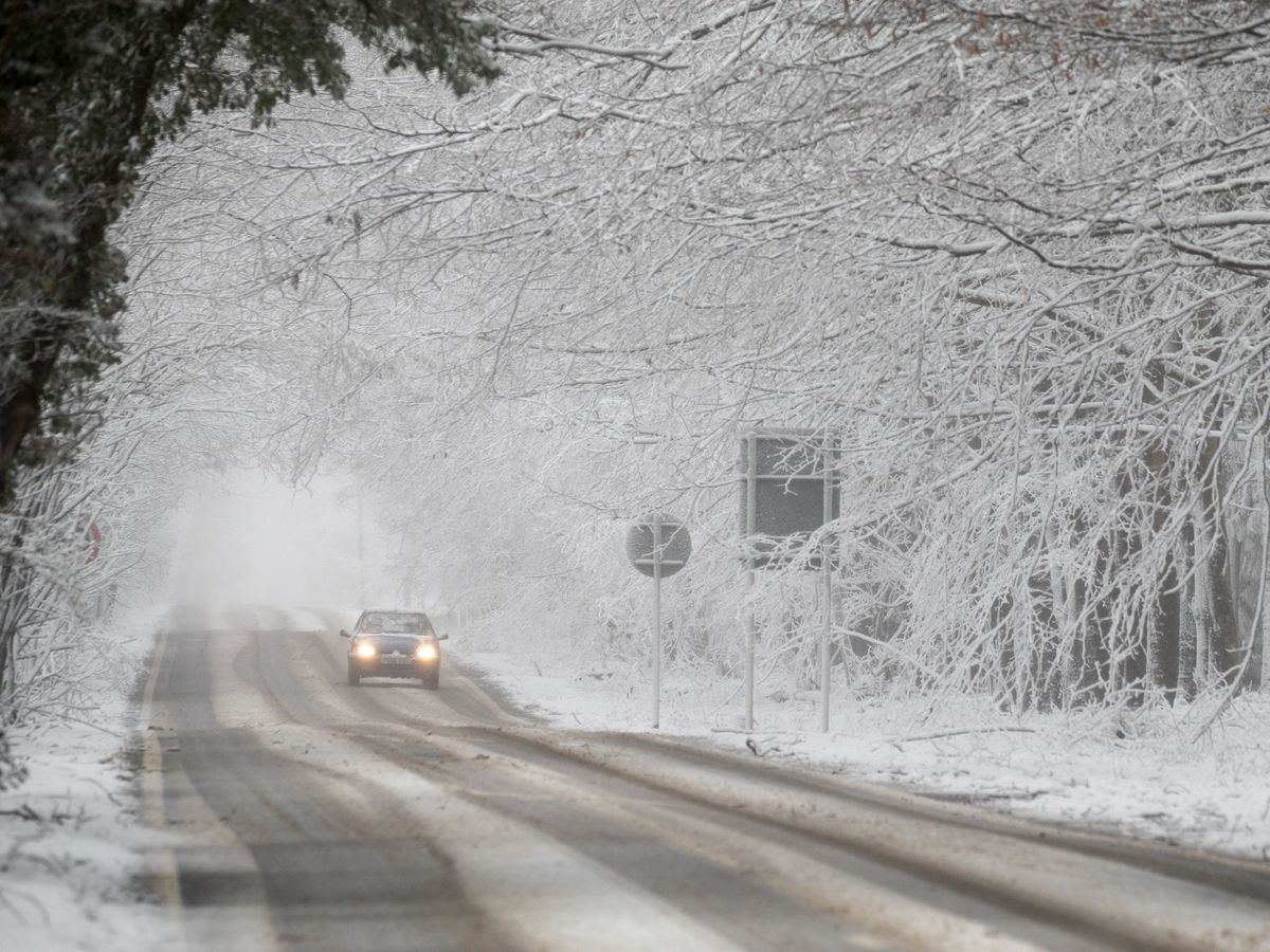 A car makes its way along a snow-covered road in Kent