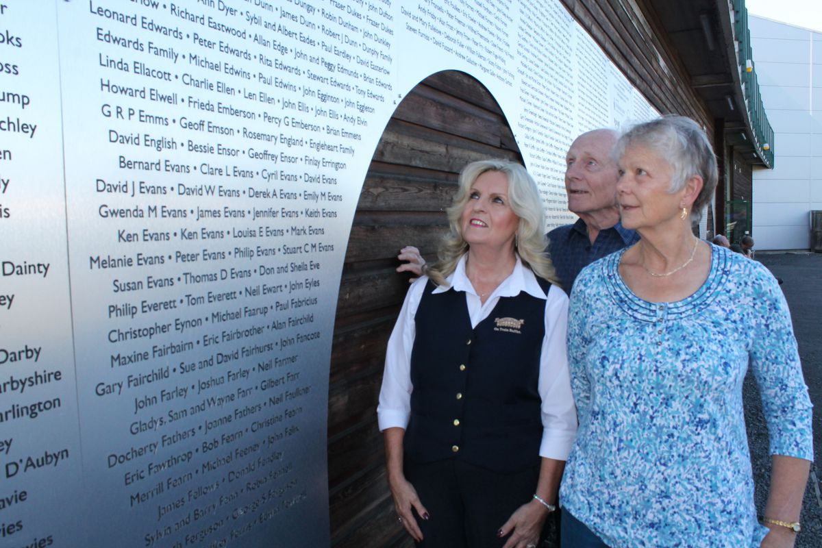 Sandra Higginson, Geoff and Hilary Boyle look on at the donor recognition wall