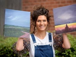 Stephanie sets up paintings' raffle draw for good causes