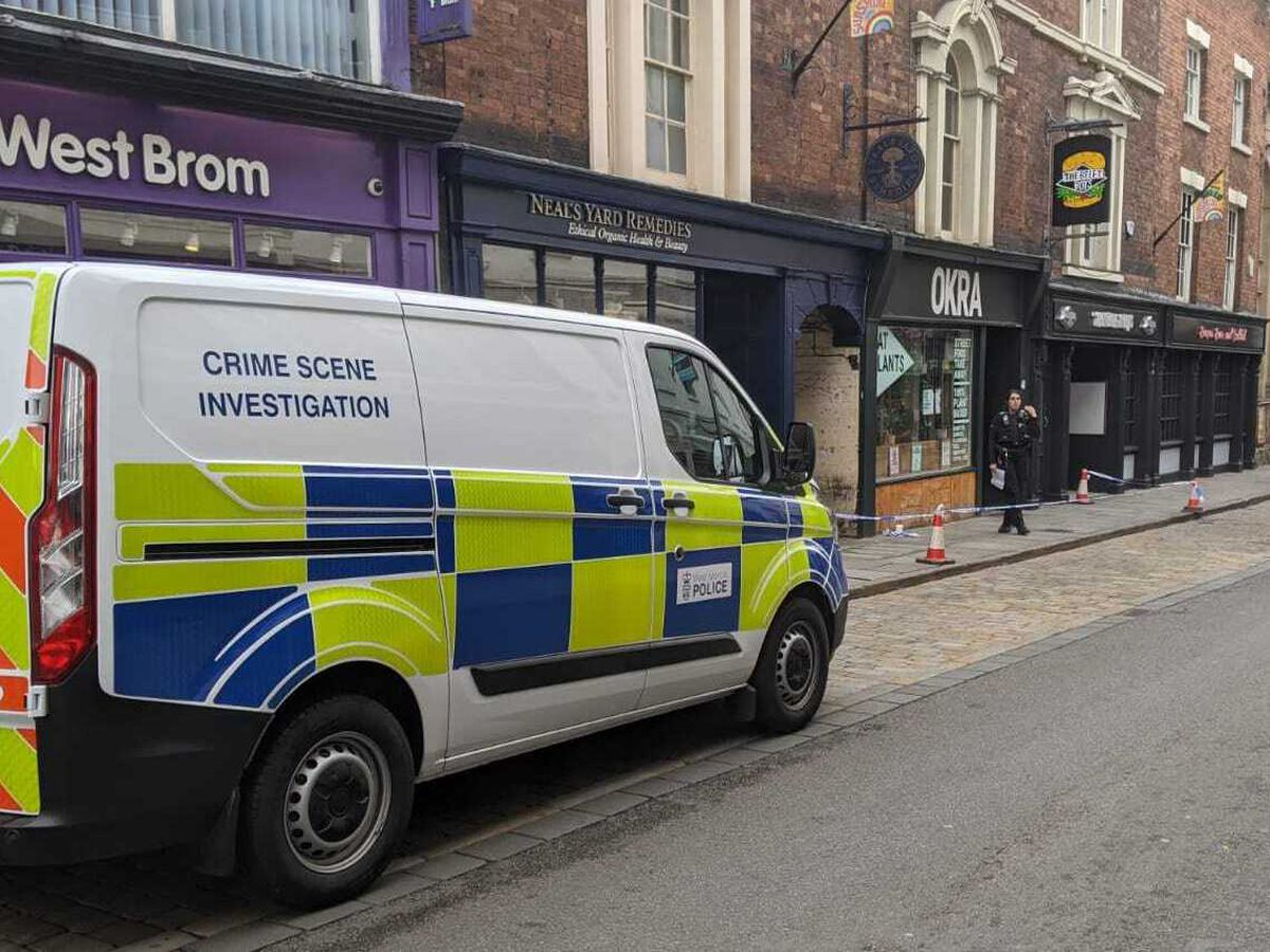 The scene on High Street where police have taped off a section of pavement and access to an alleyway