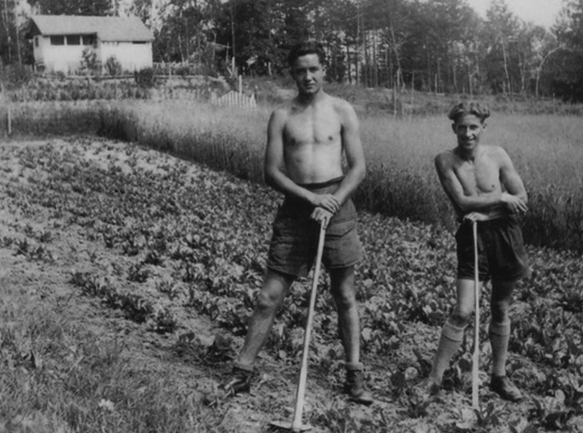Jack, left, working in a farm field in Austria. The other prisoner is Fred Lang.