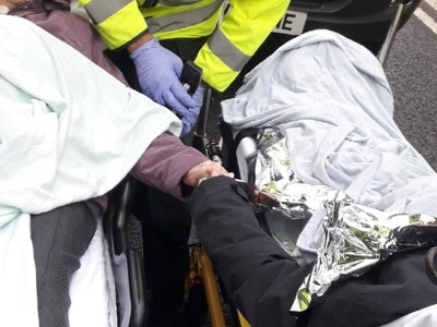 Elderly couple pictured holding hands after being rescued from car crash
