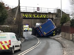 Road blocked and trains delayed after bridge crash lorry overturns