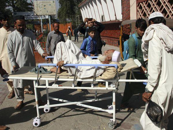 Afghans bring a man injured in a stampede to a hospital