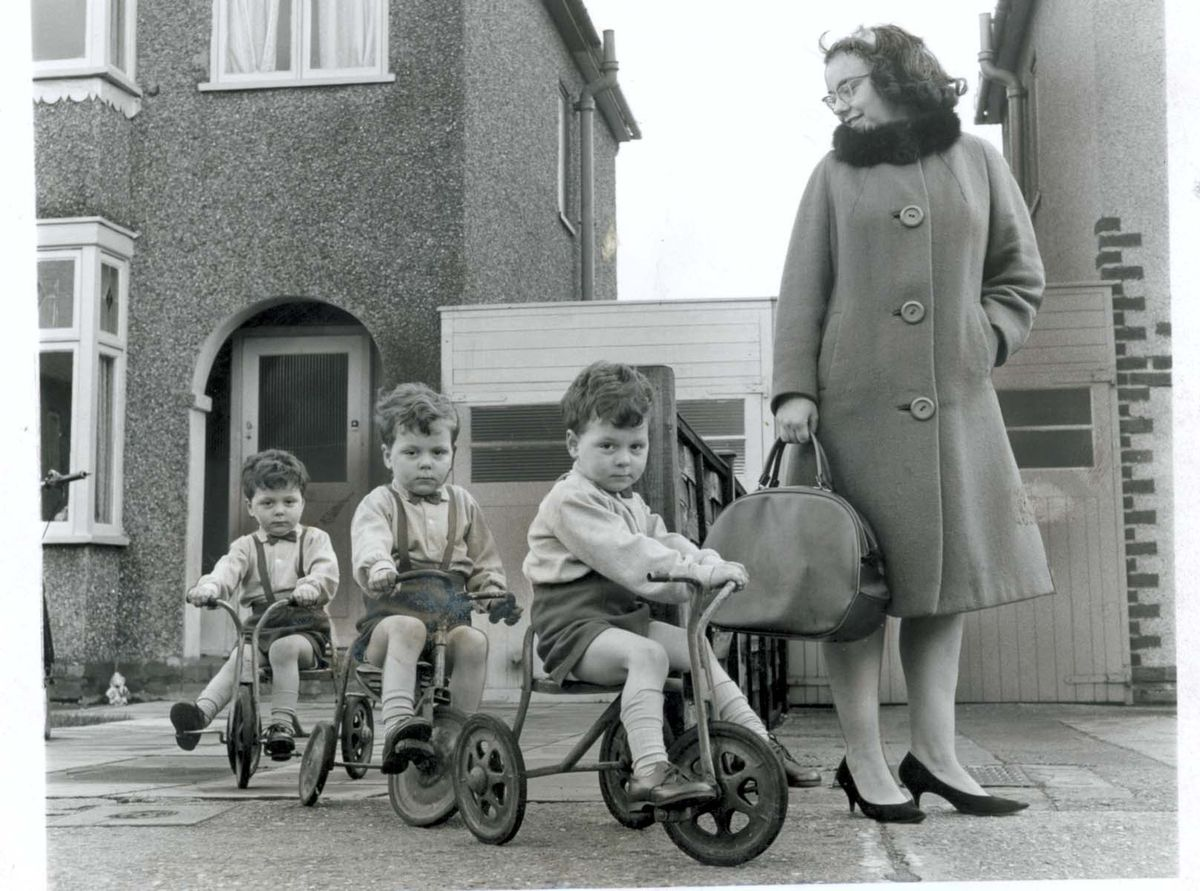 The Tunney triplets, left to right, Martin, Paul and Andrew, pictured outside their home in Chester Avenue, Tettenhall, on their fourth birthday in 1965, with proud mother Pauline Tunney, on the way to stock up the party larder