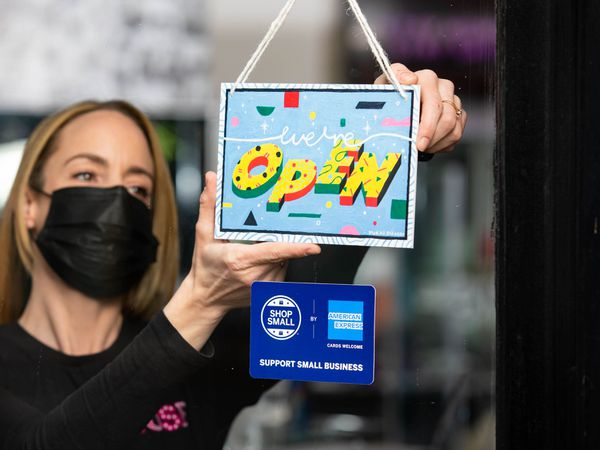 Shop owner with 'open again' sign