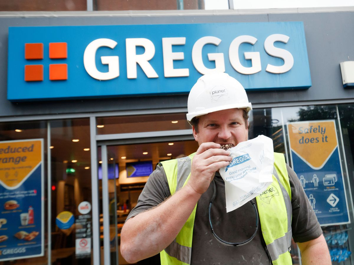 A customer outside a branch of Greggs