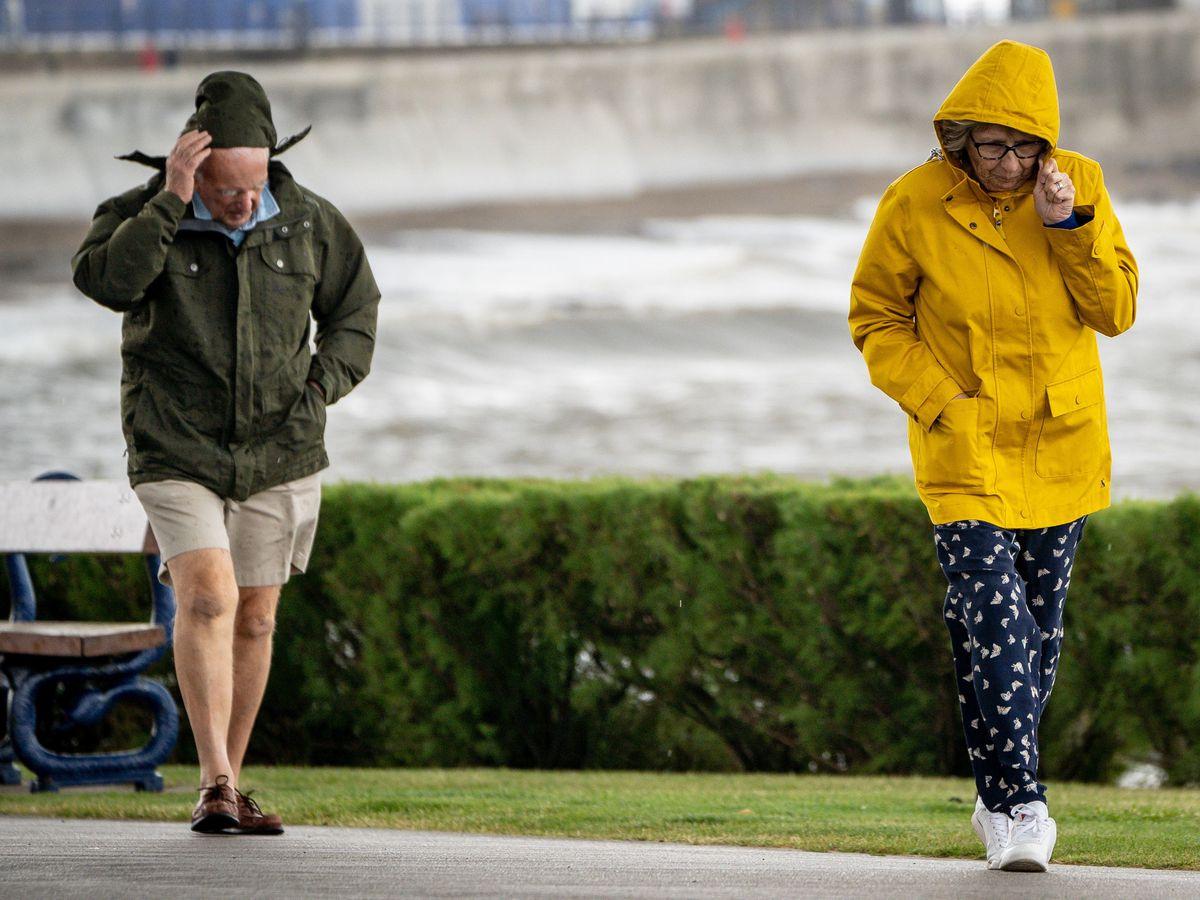 People walk in windy weather