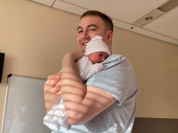 Ross Peters holding new baby