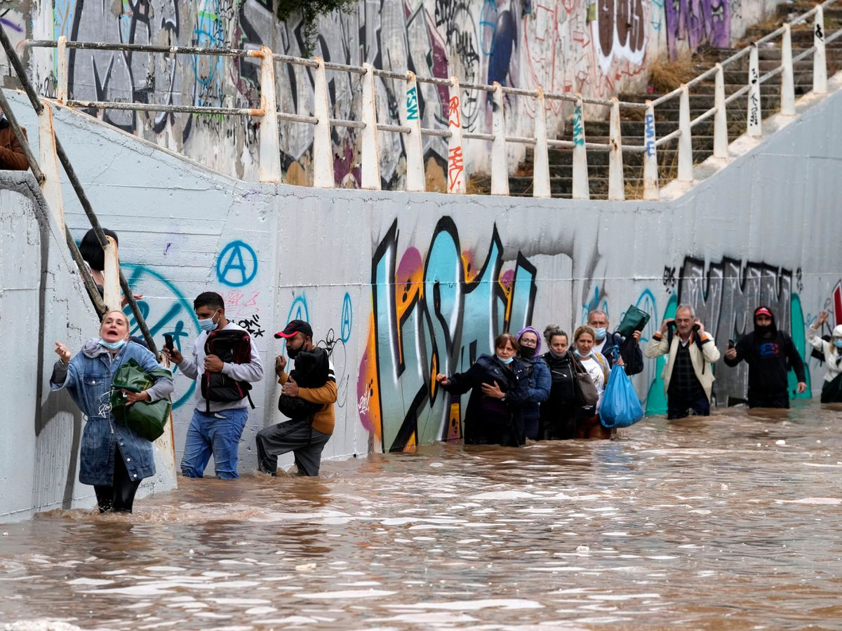 People wade through water in Athens