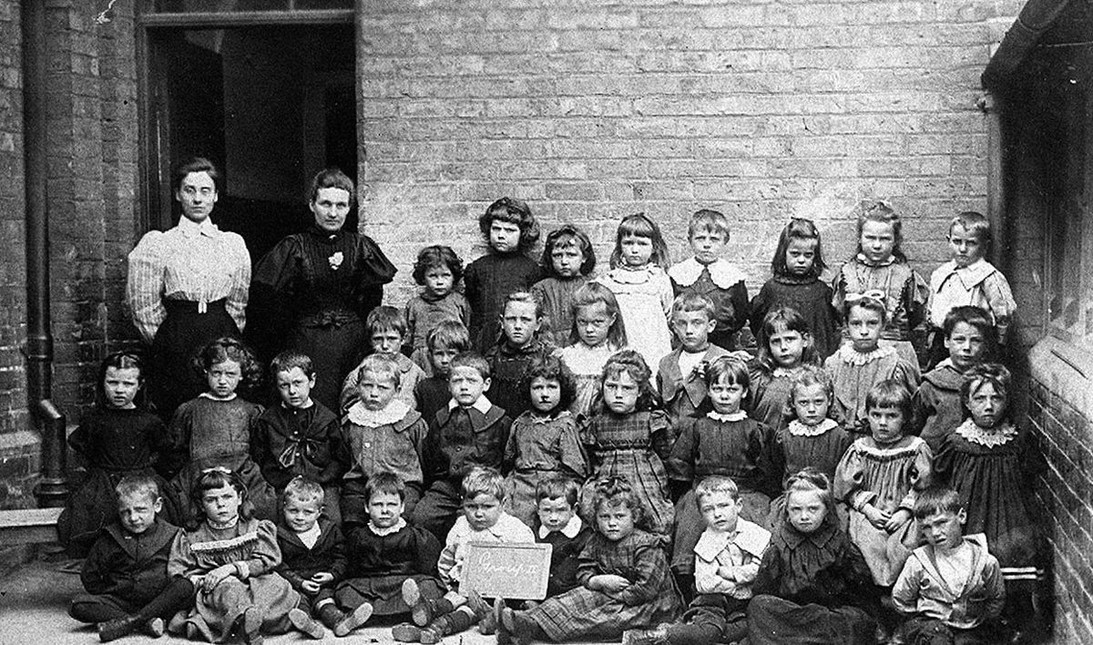 """Happy schooldays in Shrewsbury, although going by the expressions, they were perhaps not quite as happy as they might have been. This is Wyle Cop School, and the picture is marked """"Mother x in front row"""" – the girl marked with an x, front second from left, was Alice Pemberton, also known apparently as Alice Young Pemberton. Her son was Neville Nelson, and this photo was originally loaned to us back in 2003 by his widow, Mrs Pirkko Nelson. While the date of the picture is not known it is perhaps around 1902."""