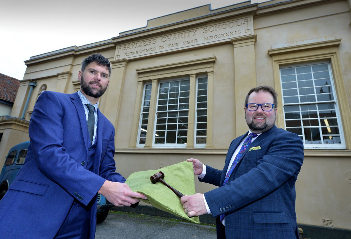 Chris Aston passes over the gavel to Thomas Forrester outside the auction house
