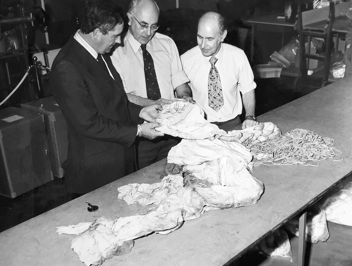 David, left, shows the wartime Irvin parachute recovered from the crash site to Ian Wright, Irvin's quality assurance officer, and, right, chief packer Frank West. David says the parachute hangs in the company's front hall display.