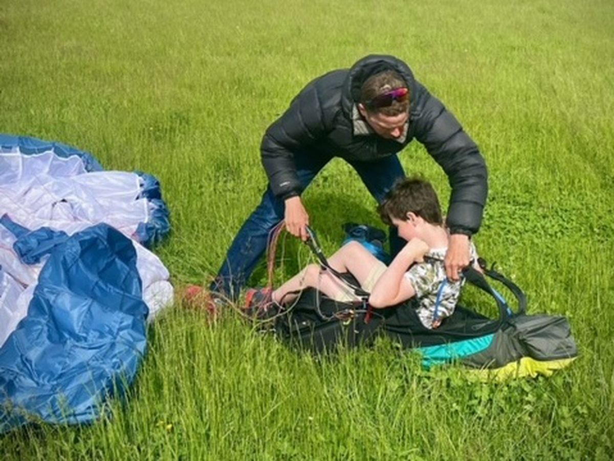 Hugh Miller shows Albie Greenway, 9, how to use paragliding equipment