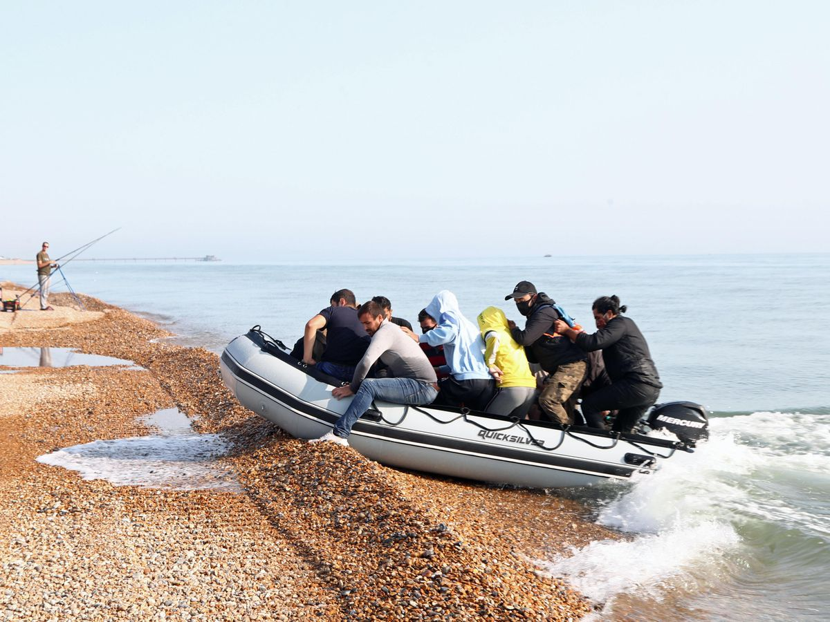 A group of people thought to be migrants arrive in an inflatable boat at Kingsdown beach, near Dover