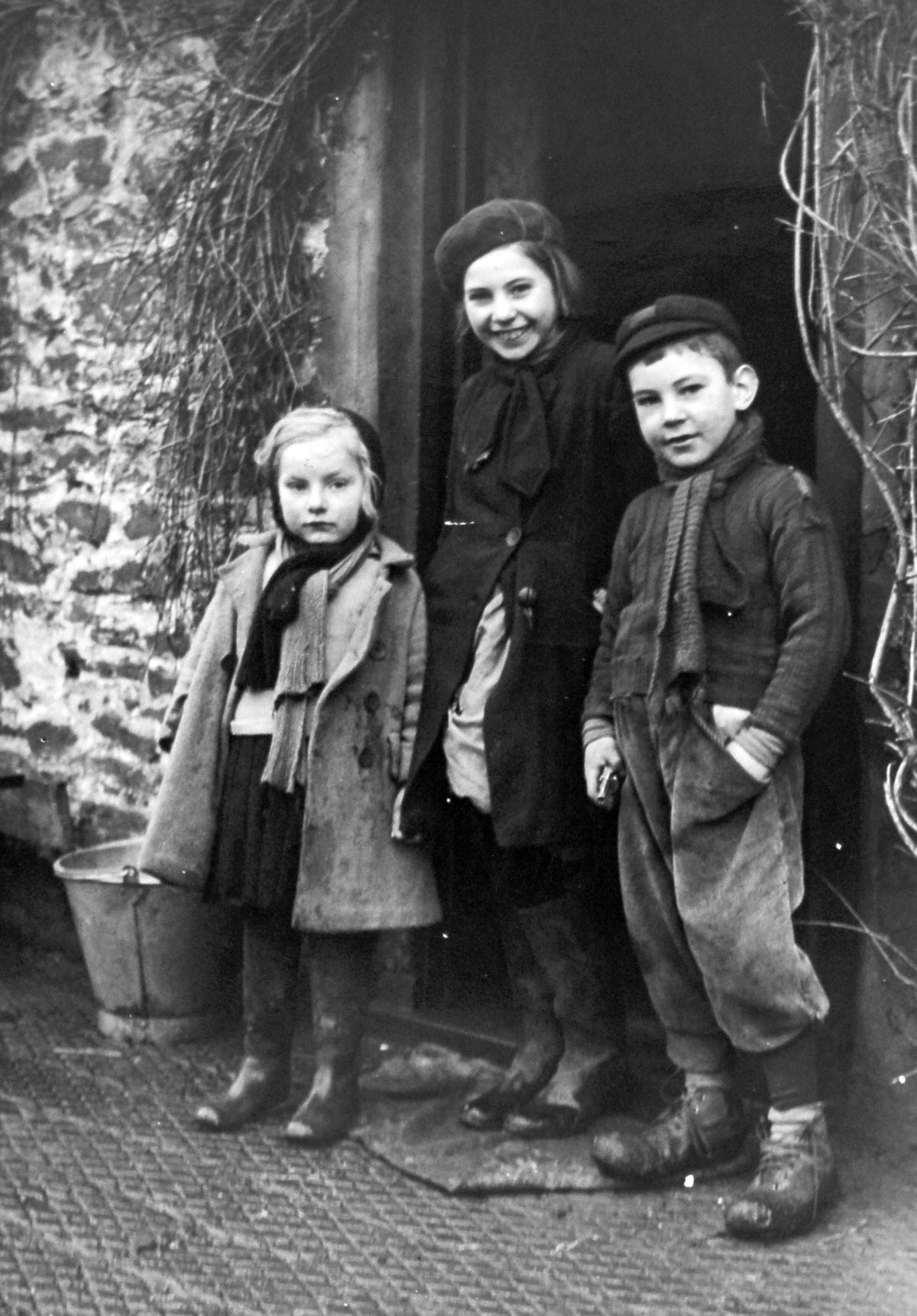 June's refugee pal Maria, centre, flanked by two other Hoorne children, Gabriel, left, and August, at the door of their cottage in Chesterton
