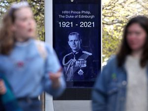 Members of the public walk passed an advertising board in Glasgow displaying a picture of the Duke of Edinburgh.