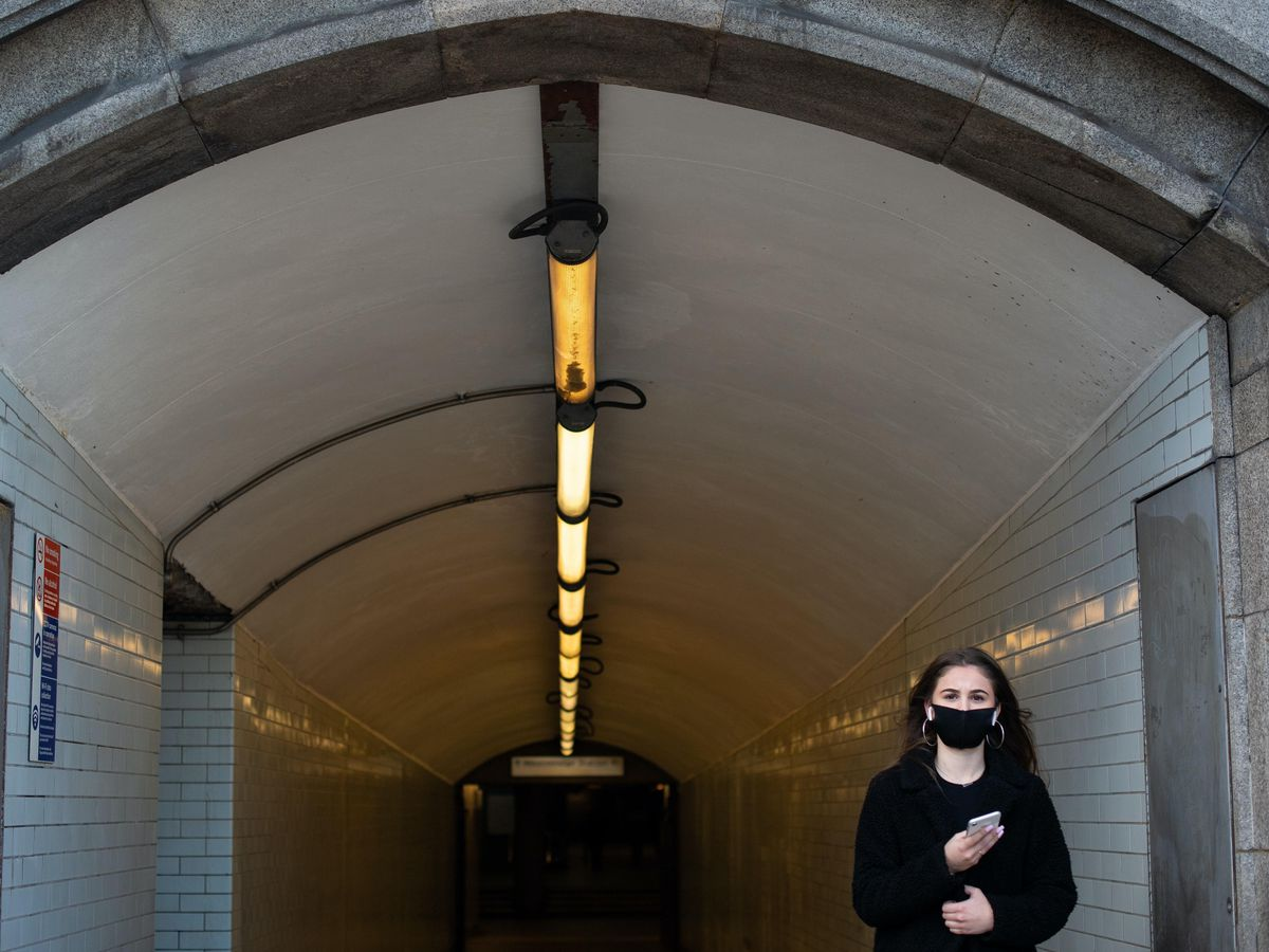 A woman wearing a protective face mask exits a subway in Westminster, London (Dominic Lipinski/PA)