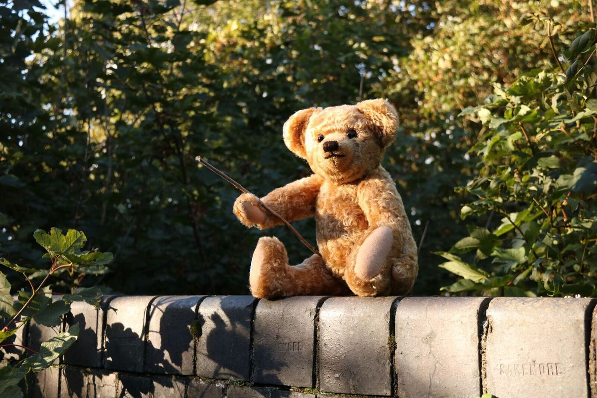 Edward bear, made by Merrythought, with a Pooh stick