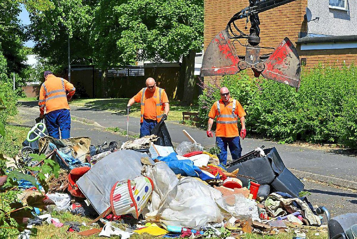 A team of council workmen clearing away a large pile of rubbish that was fly-tipped at Stebbings in Sutton Hill, Telford