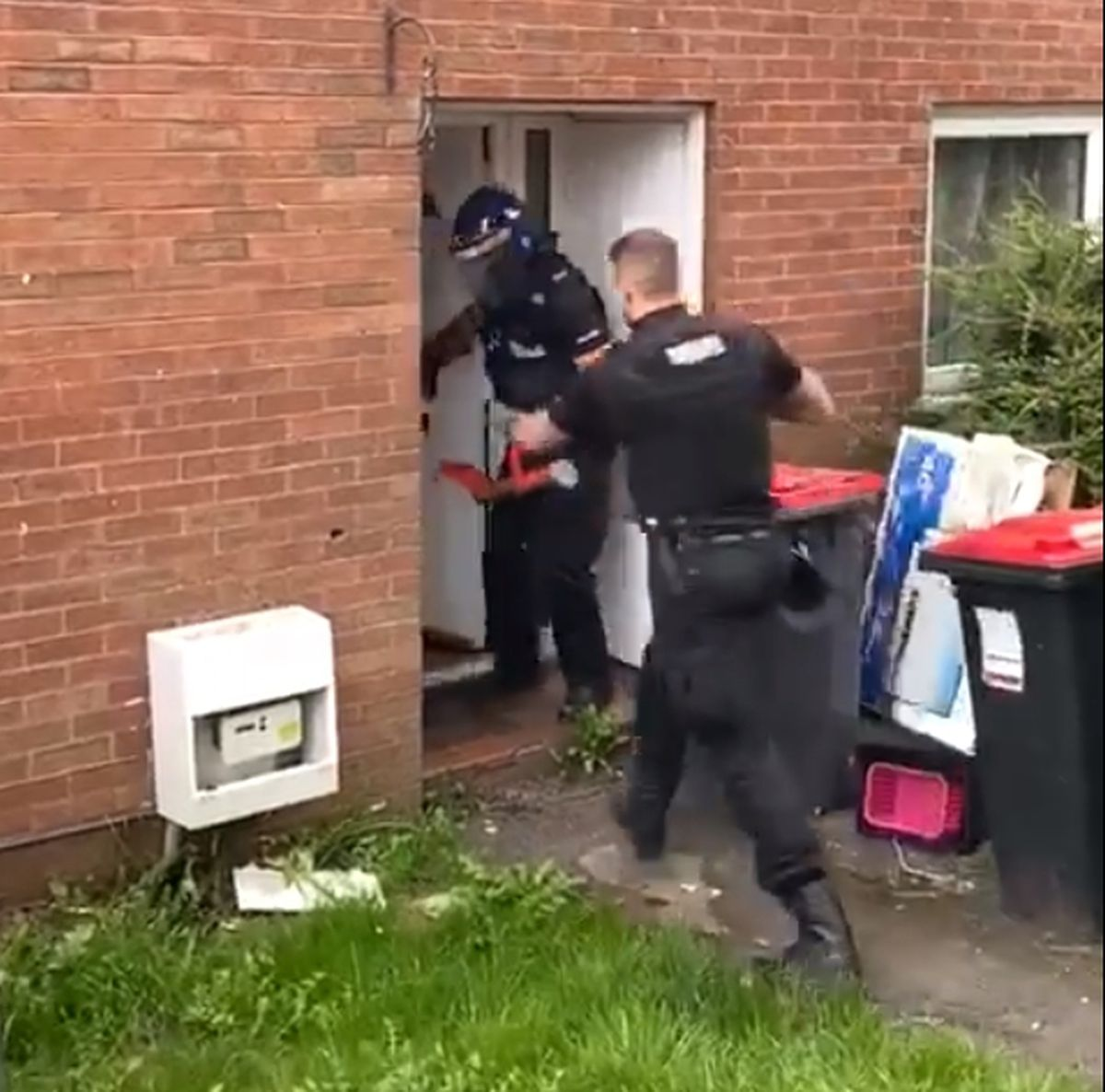 Police smash their way in through the front door