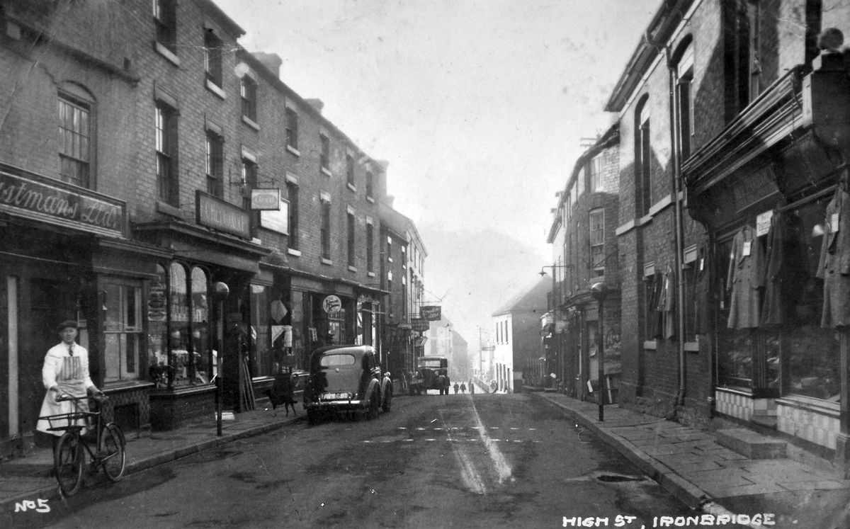 High Street, Ironbridge, in the 1930s, as seen in an old postcard in the possession of Pete Edwards, of Stirchley. Pete says his late mother told him that the car of his grandfather, Eddie Lloyd, is on the picture, but he does not know which of the two cars is the right one. Whichever it is, it is parked outside Eddie's electrical goods shop which was at 28 and 29 High Street. In the mid-1930s Eddie set up an aerial and equipment on top of the Meadow Pit Mound in Madeley and successfully picked up television pictures broadcast from London.