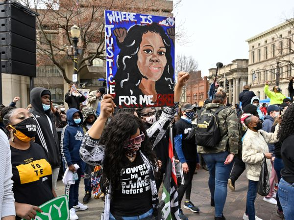 A protester holds up a painting of Breonna Taylor during a rally on the one year anniversary of her death at Jefferson Square Park in Louisville