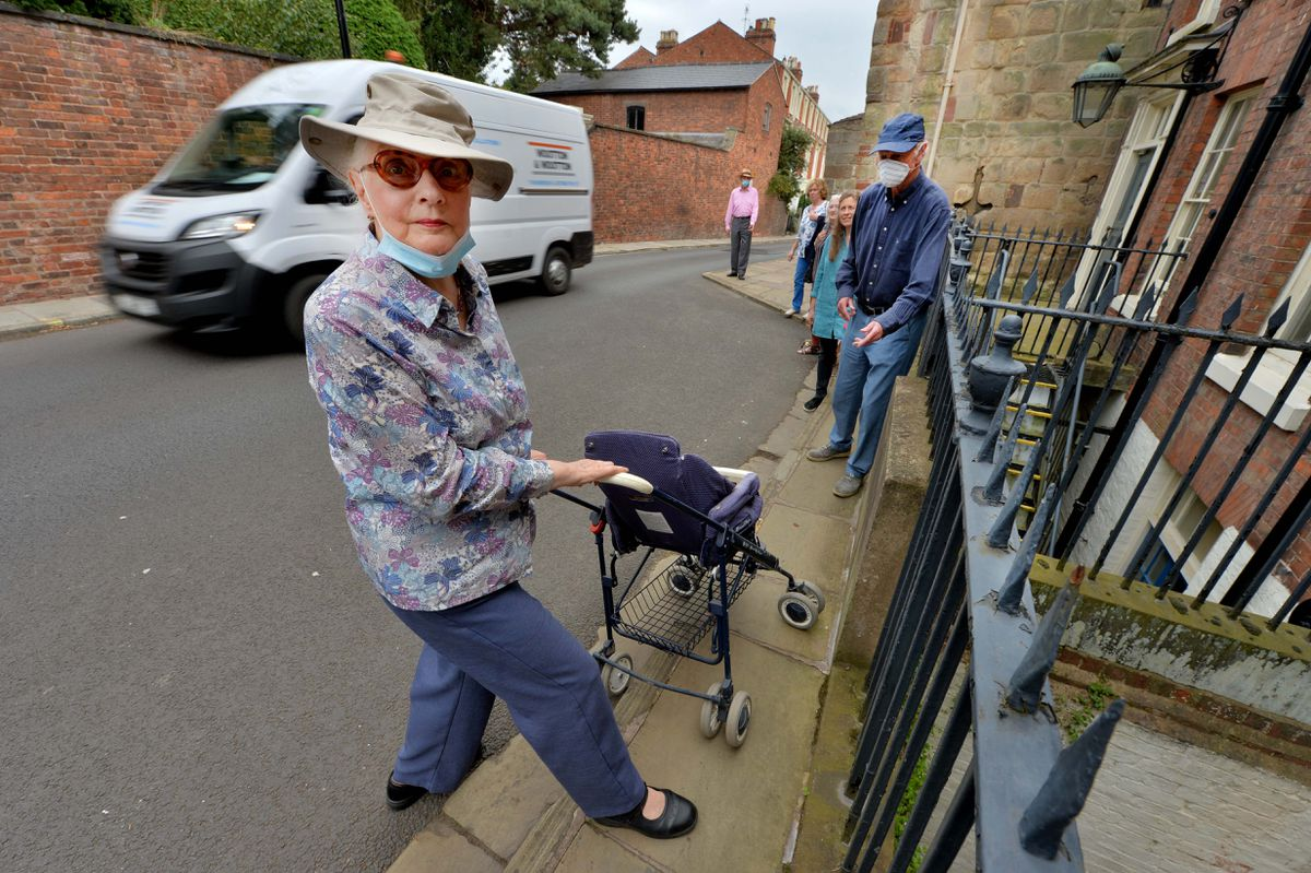Lucy Shrank attempts to push a pushchair onto the pavement