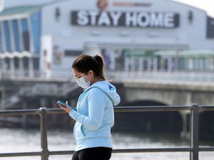 A woman wearing a mask looks at her mobile phone