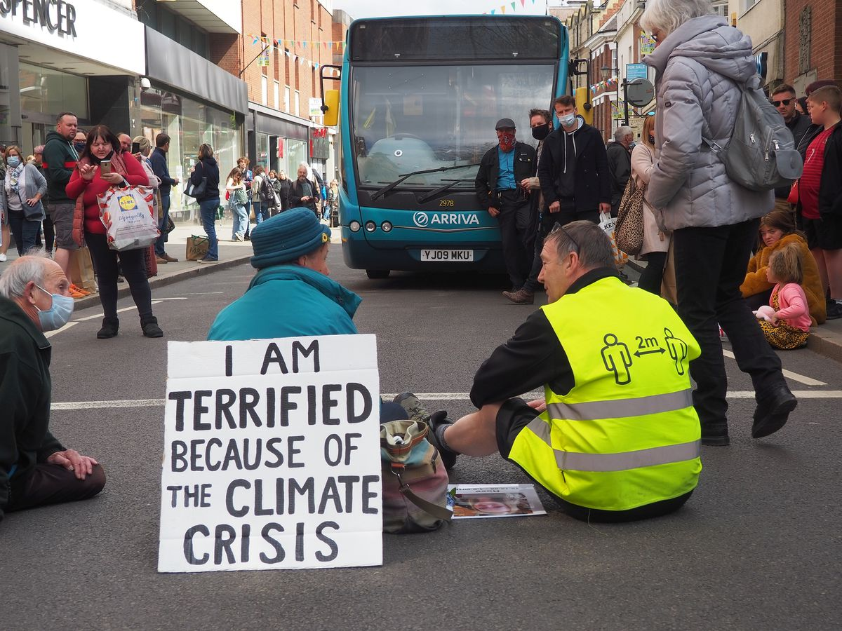 An Arriva employee sitting with the protester. Photo: Phil B