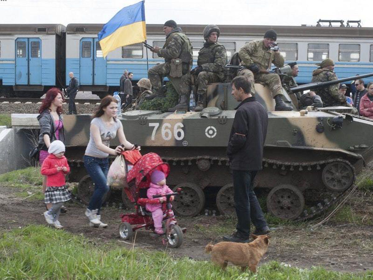 People walk past a Ukrainian army combat vehicle parked near a railway in Kramatorsk, Ukraine, in 2014