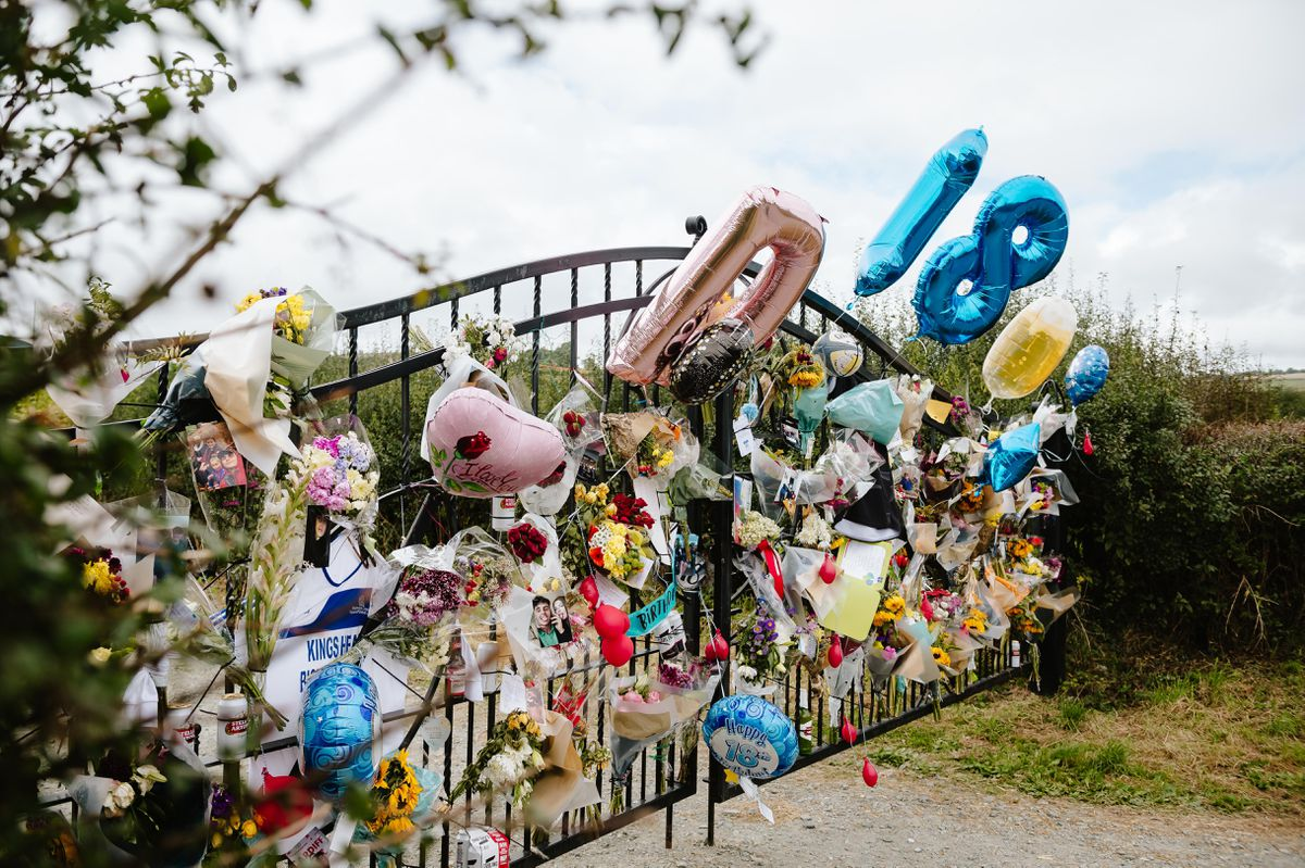 Floral tributes and birthday balloons at the gates of the rugby club