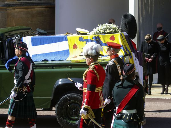 The Duke of Edinburgh's coffin, covered with his Personal Standard, is carried on the purpose built Land Rover Defender at the funeral