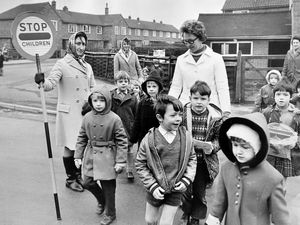 nostalgia pic. Oswestry. This is a print in the Shropshire Star print archive and was taken on January 28, 1972. The caption pasted on the back reads: 'Taking over while the official crossing warden is ill, members of the Tufty Club junior road safety committee help Oswestry County Infants' pupils across a busy road near the school. Here Mrs B. Johnson sees the children across the road, helped by Mrs Joy Baskerville.' Date written by the caption is 29.1.72, which will be publication date, i.e. January 29, 1972. The print has the Shropshire Star copyright stamp and the photographer was Bill Bishton. Road safety. Lollipop lady. Lollipop ladies. School crossings. Library code: Oswestry nostalgia 2016..