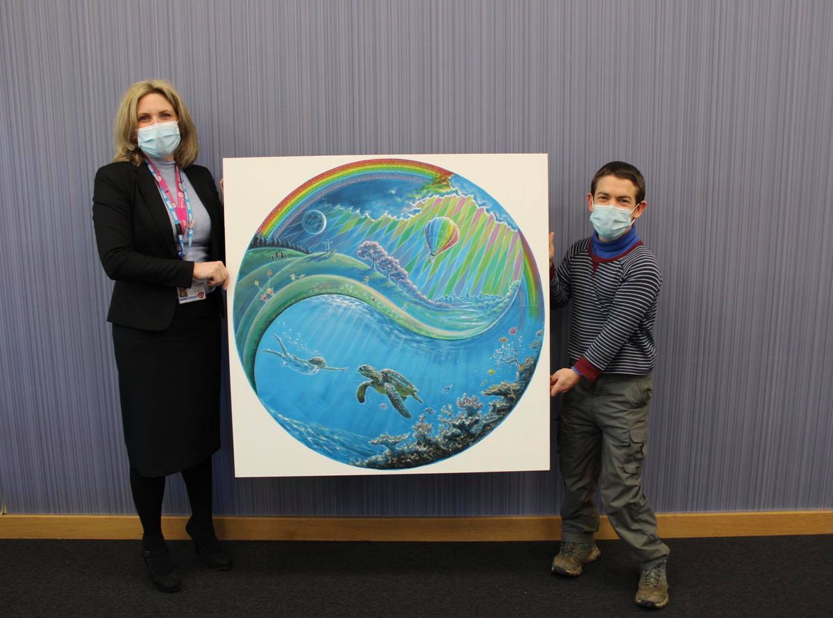 Victoria Sugden, League of Friends Charity Director, with Rory McCann and the piece of art, donated to the hospital