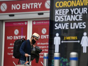 A passenger at Birmingham Airport, as people arriving into England from holidays in Spain have been told they must quarantine when they return home. PA Photo. Picture date: Monday July 27, 2020. Spain has been removed from the UK's list of safe destinations after it saw a spike in the number of coronavirus cases. See PA story HEALTH Coronavirus. Photo credit should read: Jacob King/PA Wire.