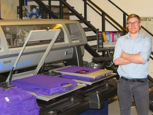 Operations director Sam Mason standing next to Kingfisher's DTG printer