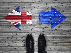 Brexit, flags of the United Kingdom and the European Union on wooden background with legs and shoes
