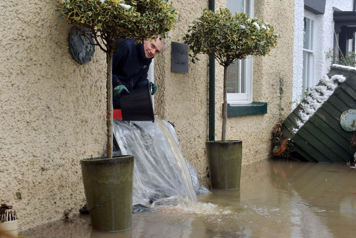 Jeremy Timmins bails water out of his flooded home in Bewdley