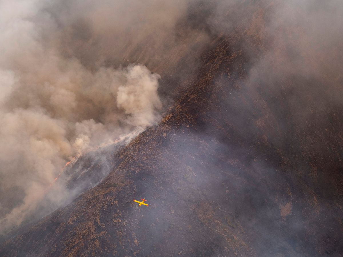 A seaplane flies over a wildfire in southern Spain