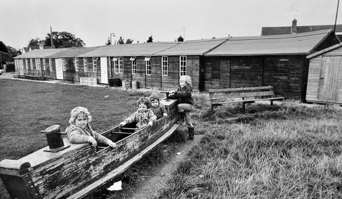 """Children play outside the old Bicton village hall in October 1974. At the time villagers had far-reaching plans for a new village hall. According to the story carried with this picture: """"The present hall, which is in almost constant use, is an ex-wartime building which was erected in 1951 in a field bought with £600 of the £1,000 villagers raised between 1943 and 1950."""" The old hall was still standing in February 1976, but by then the new hall was moving into the final stages of completion."""