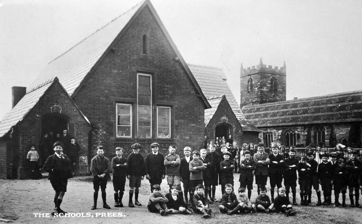 """If you think these boys at Prees village school look a bit tough, just look at the girls – they've had to fence them in. This postcard from the collection of Ray Farlow showing """"The Schools, Prees"""" – plural because there would have been separate boys' and girls' sections – was franked at Prees on April 25, 1928, and was addressed to Mrs H Hopwood, Royal Alexandra Home, Rhyl. The message was: """"My dear Mama, just a little card to tell you we are alright – with kind love & kisses & hope you are better, from Tony xx."""" This building is still the village school today."""