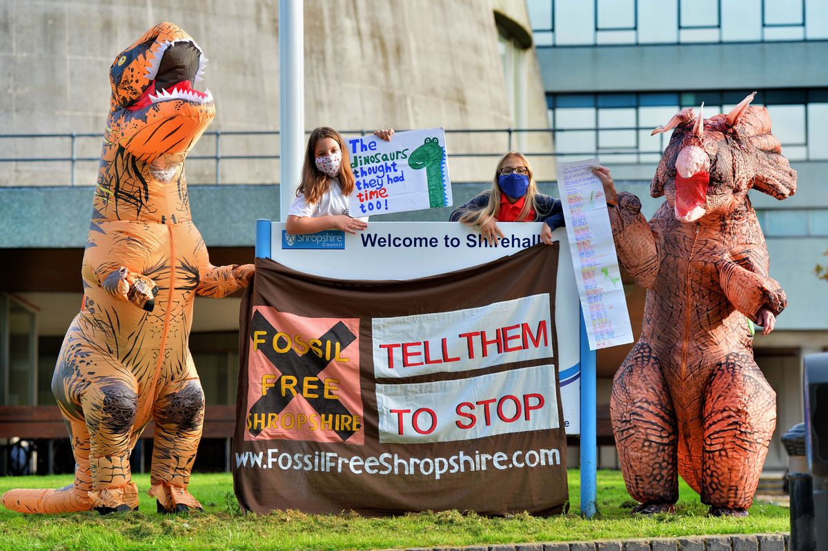 Youngsters Alice Russell 9, and Ana Russell 9, were joined by dinosaurs to hand in a petition asking the council to think about their investments into fossil fuel companies.