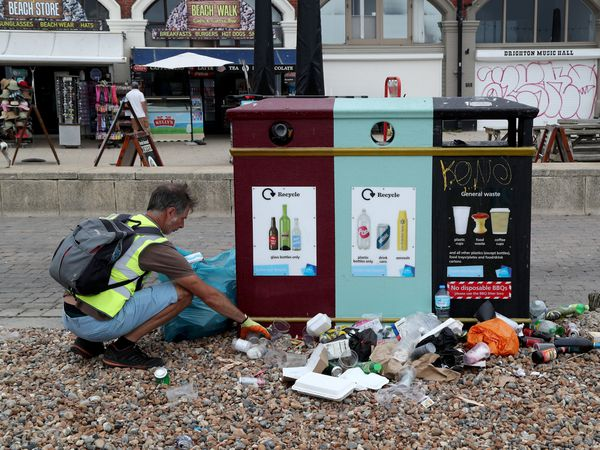 A man clears rubbish left by beachgoers in Brighton